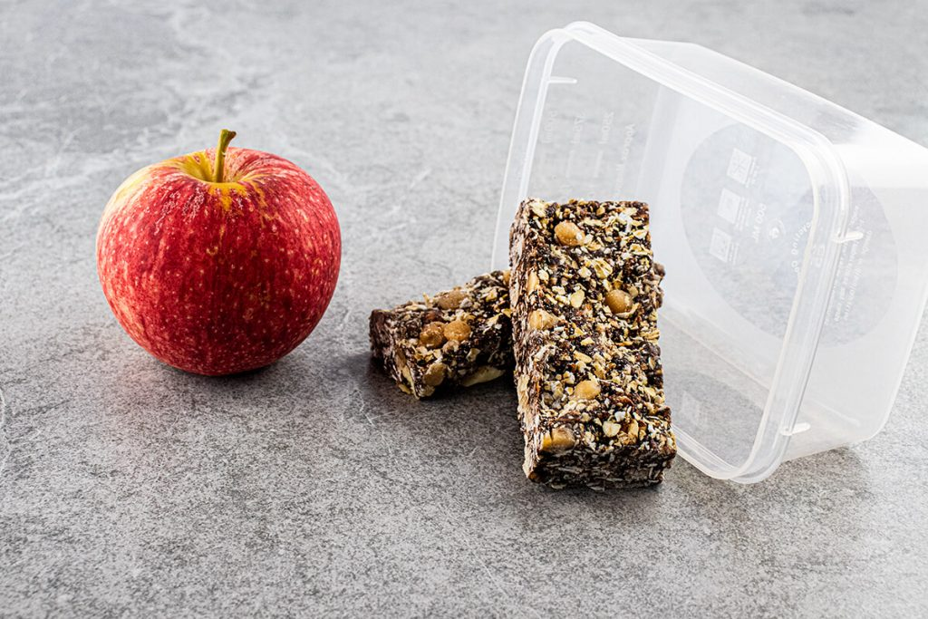 Grey slate background with lunchbox inspired setting (apple and reusable container used as props) with Choc Almond Fudge Museli Bar