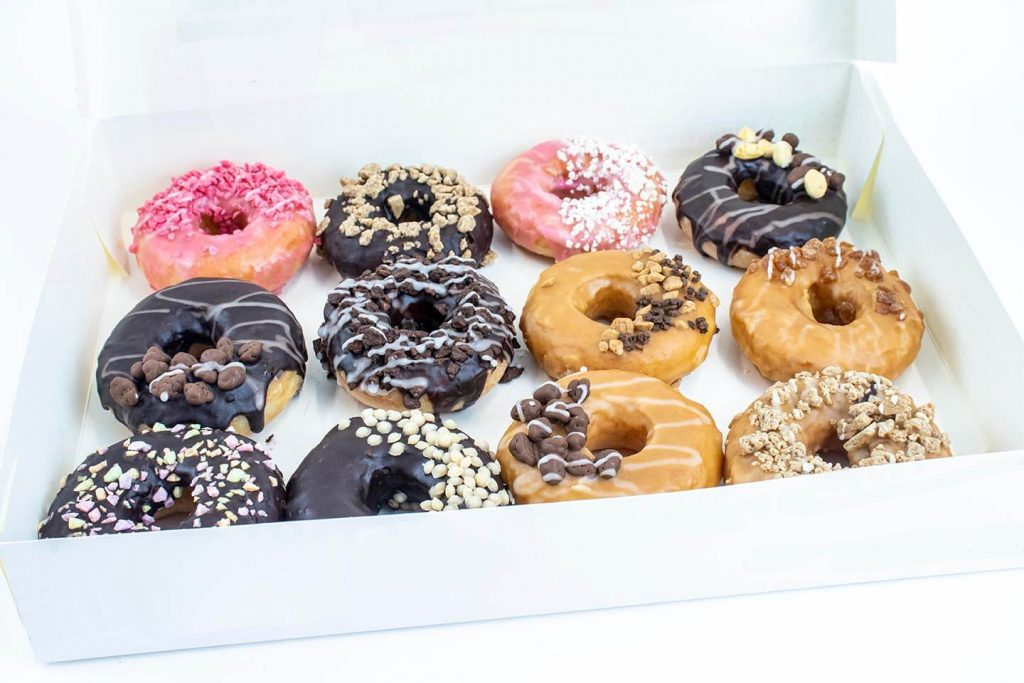 Box of 12 mixed donuts with inclusions on white background