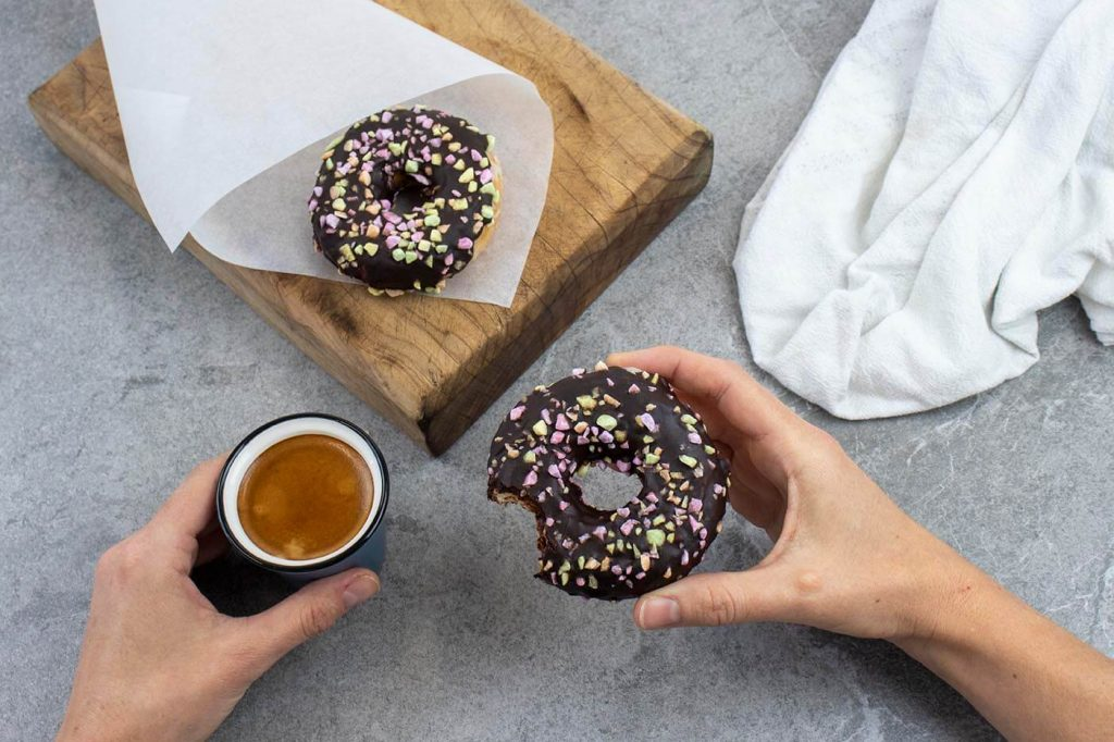 Caring Hands - Person sitting at table with coffee and two donuts, one part eaten in hand other on cutting board