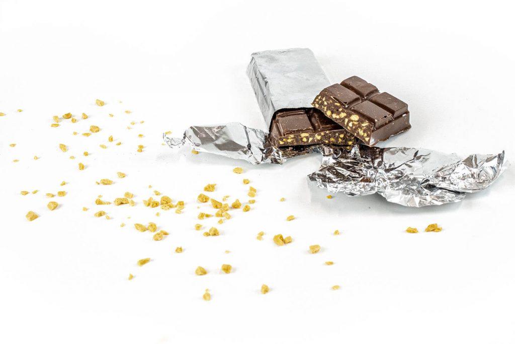 Choc Honeycomb bar sprinkled honeycomb inclusions on white bg