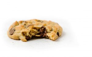 chocolate chip cookie with bite taken out of it on white background