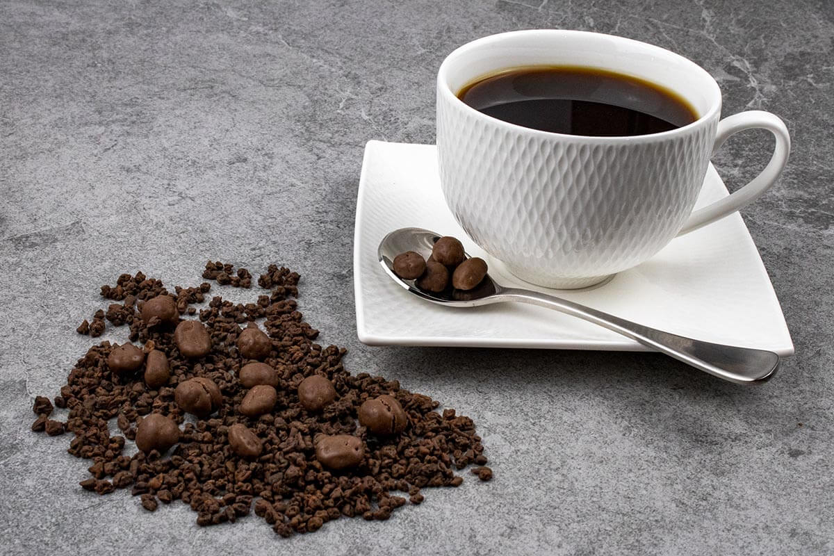 Grey slate look tile with white coffee cup and saucer in right hand corner. Teaspoon of choc coated coffee beans resting on saucer. Chocolate coated coffee beans and chocolate coated coffee bean kibble scattered on surface of background