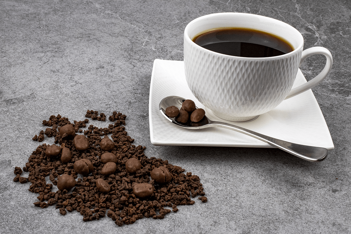 Mocha Inspiration - Chocolate Coated Coffee Beans and Kibbled Coffee Beans coated in chocolate alongside a white coffee cup, and a spoonfull of chocolate beans on a grey background