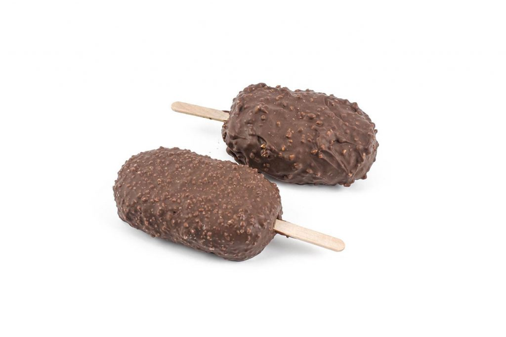 Two chocolate and inclusion coated ice cream bars on white background