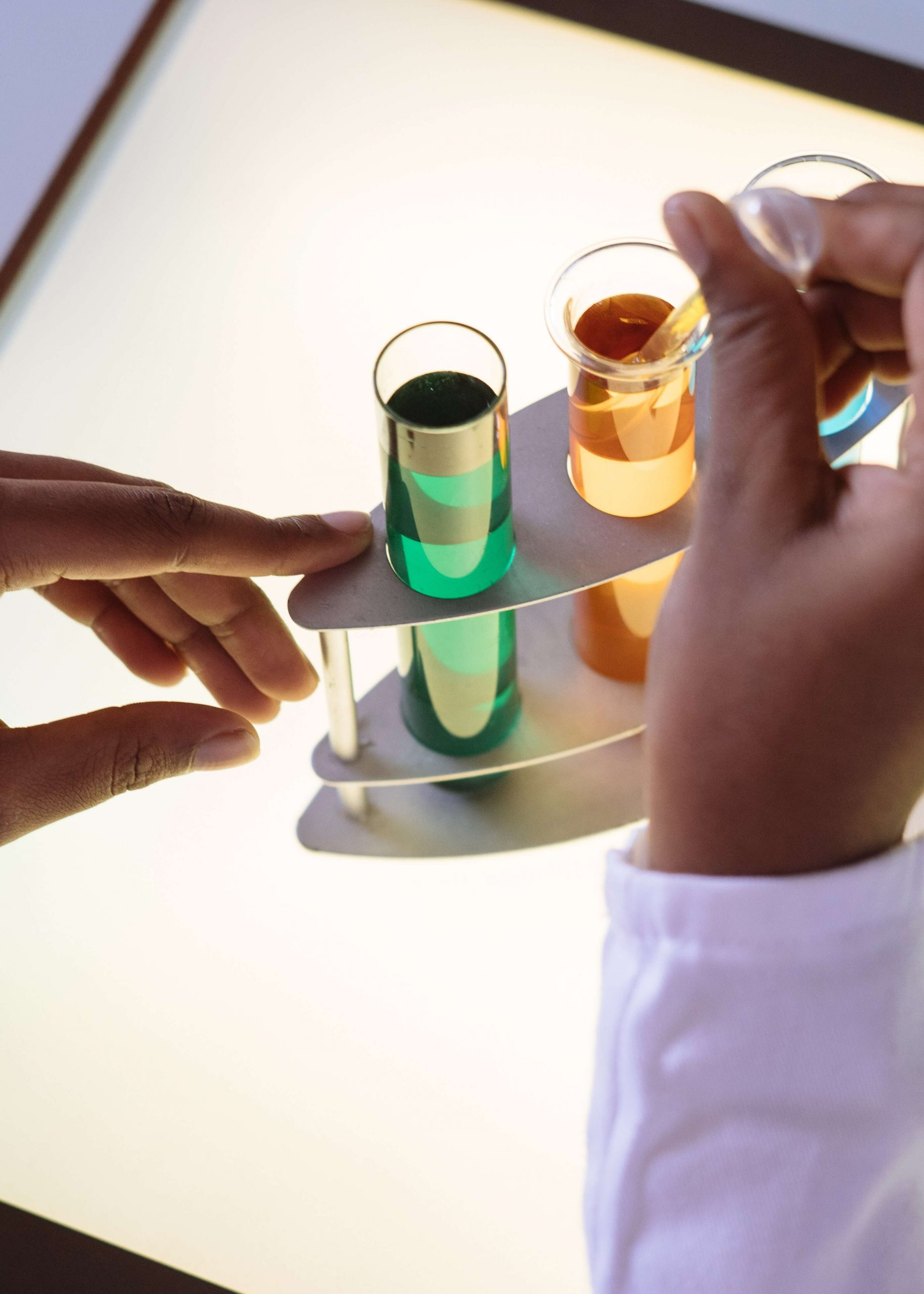 test tubes filled with coloured liquid being examined by unrecogniseable chemist
